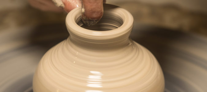 light brown clay pot being made by potter