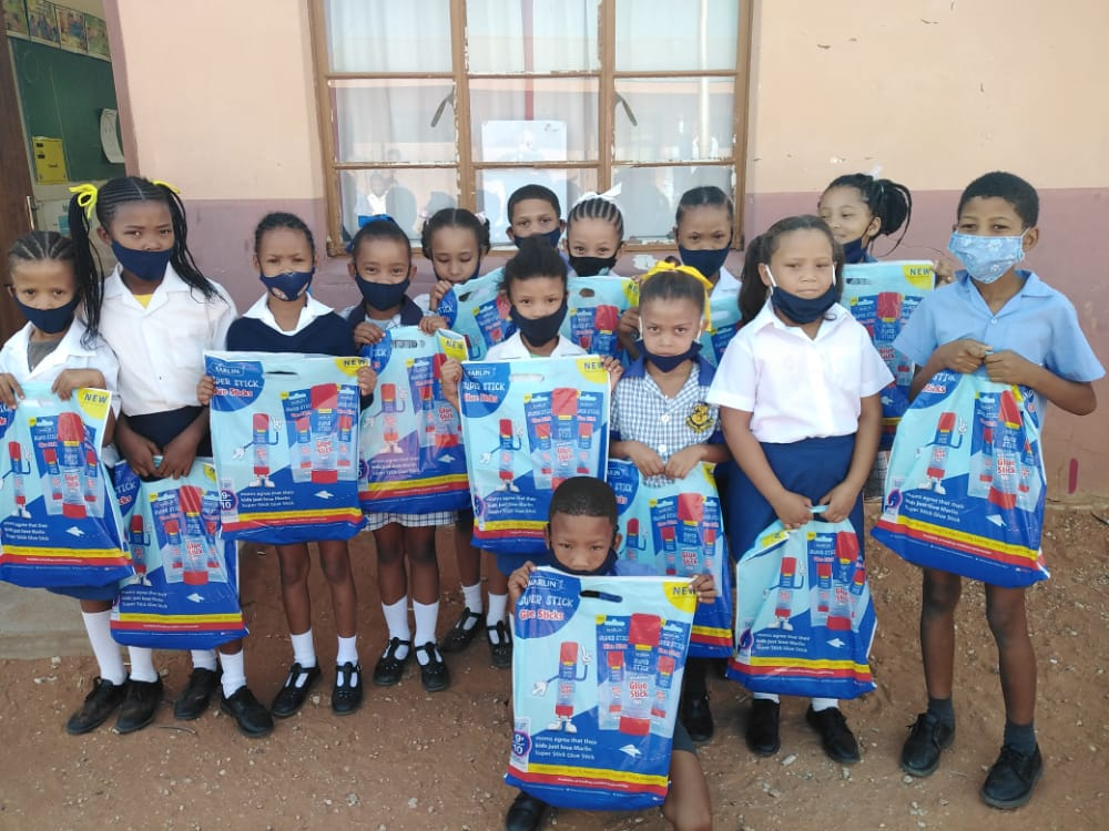Small children standing in front of a classsroom with packages filled with school utensils