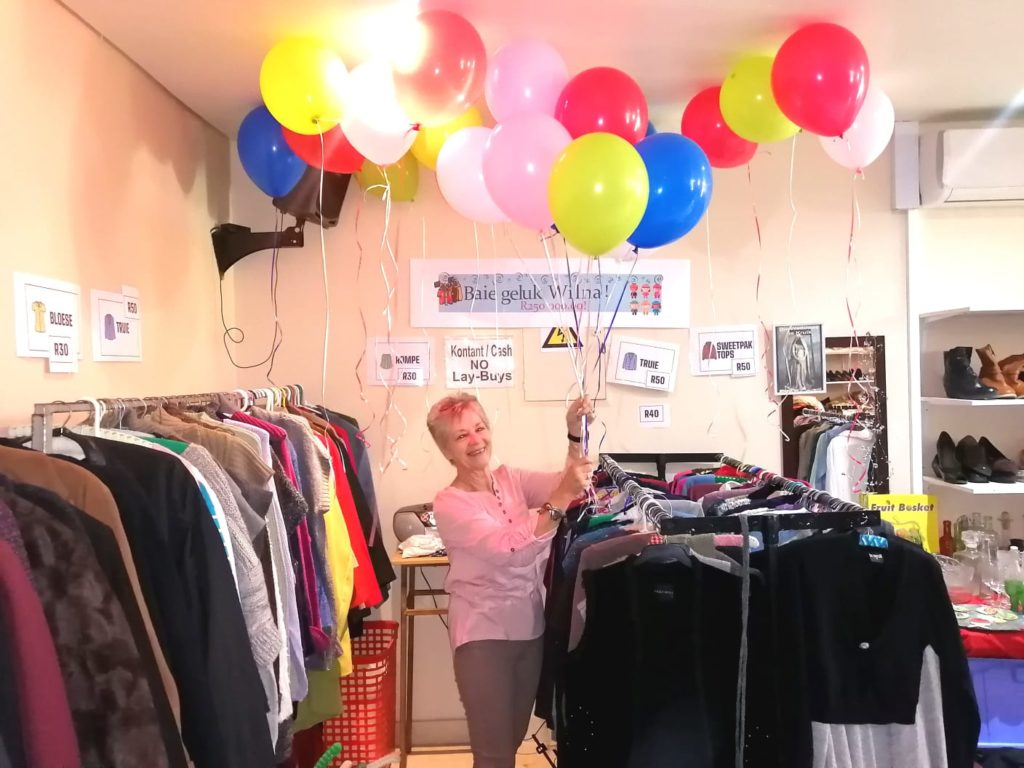 Wilna Deacon standing in the church's shop with baloons floating above her head and a banner on the wall behind her wishing her a happy birthday